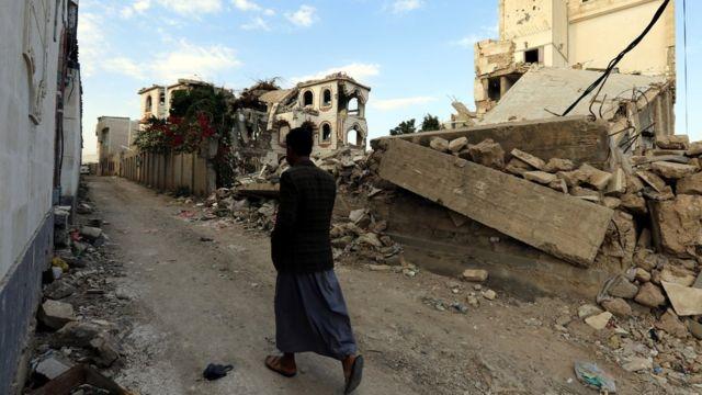 (أرشيف) رجل يمشي بجانب أنقاض مبنى دمر جراء غارات للتحالف بقيادة السعودية في صنعاء