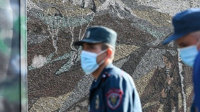 Üzlərində tibbi maska olan polis əməkdaşları