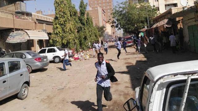 متظاهرون يفرون من قنابل الغاز المسيل للدموع في الخرطوم