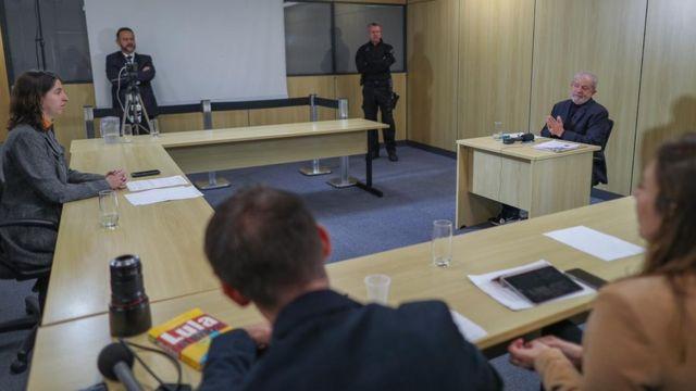 A equipe da BBC e o ex-presidente Lula em mesas, observados por agente de segurança