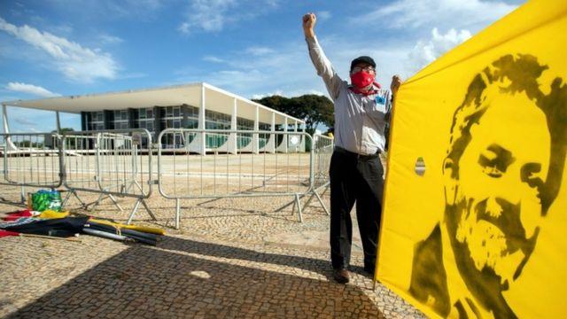 Homem em frente ao STF com braço erguido e, com a outra mão, segurando bandeira com desenho de Lula