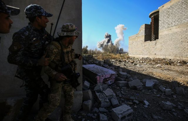 Members of the Iraqi forces take cover as smoke rises in the background during their advance towards Dindan neighborhood in the western half of the northern city of Mosul, as part of the offensive to retake the area from Islamic State (IS) group fighters, on February 25, 2017.