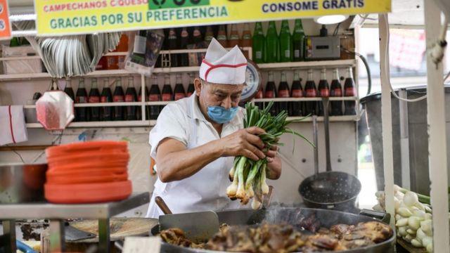 Cozinheiro manipula vegetais com máscara em barraca de comida no México