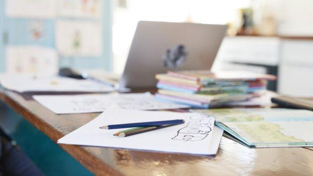 Material escolar sobre mesa com computador ao fundo