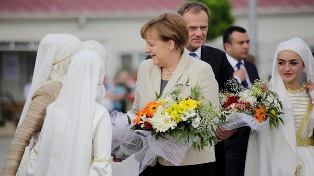 Syrian children welcomes German Chancellor Angela Merkel (C,L) and President of the European Council, Donald Tusk (C,R) during a visit to a refugee camp