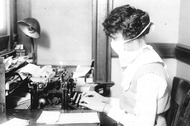 A woman typing on a typewriter in a mask in 1918