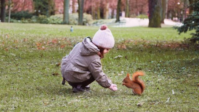Una niña y una ardilla.