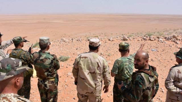 Syrian army officers and pro-government militiamen inspect the desert from Bir Qabaqib, west of Deir al-Zour (4 September 2017)