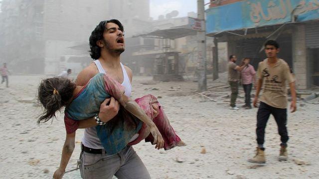Hombre carga en brazos a una niña en Aleppo, Siria.