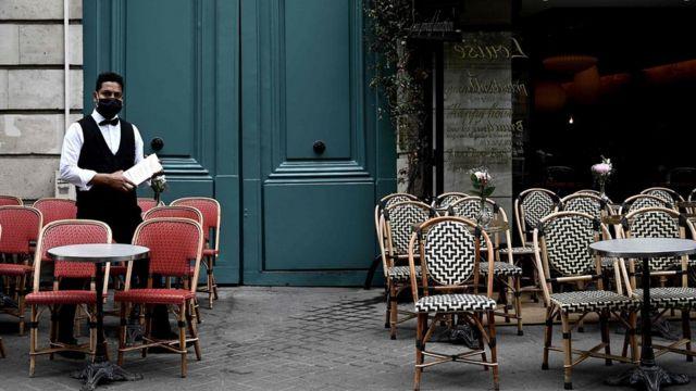 официант у входа в ресторан в париже