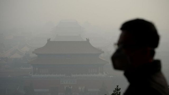 A wearing a face mask visits a park near the Forbidden City during heavy smog in Beijing