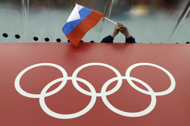 Torcedor com bandeira russa diante de logo olímpico