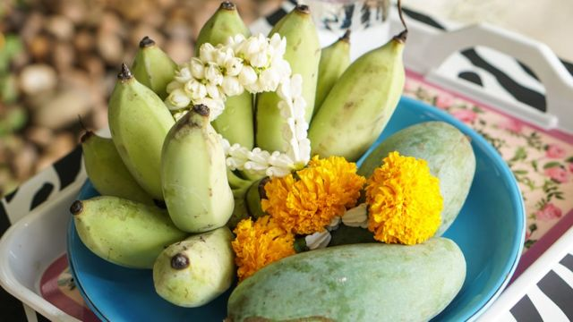 A plate containing mangoes and other fruits to make an offering to the spirits, with white garland