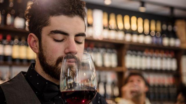 Hombre oliendo una copa de vino.