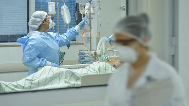 Profissionais de saúde trabalhando num leito de hospital