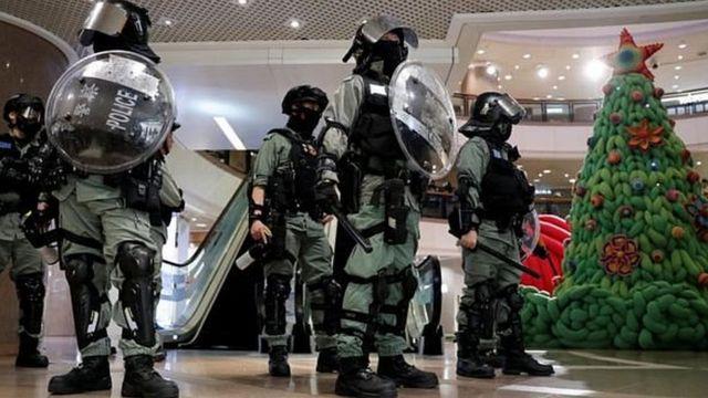 Полиция со щитами в шлемах возле украшенной елки