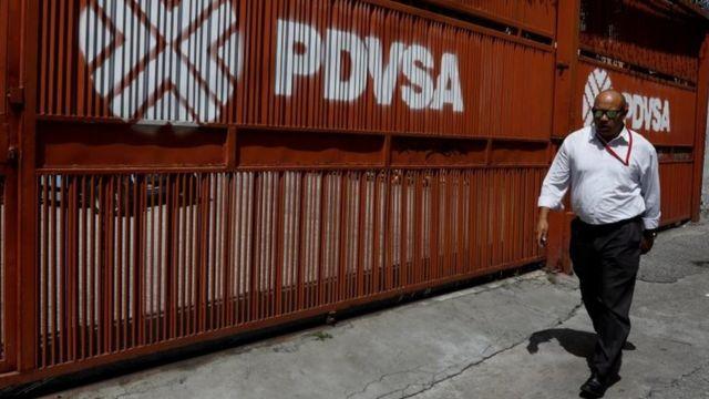 """Un hombre camina al lado de un mural que lleva pintado el logo y nombre de """"PDVSA"""""""
