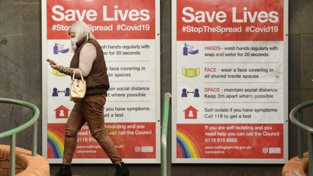"""Mujer en Londres pasando delante de un cartel en la calle que dice """"Cuídate y salva vidas"""""""