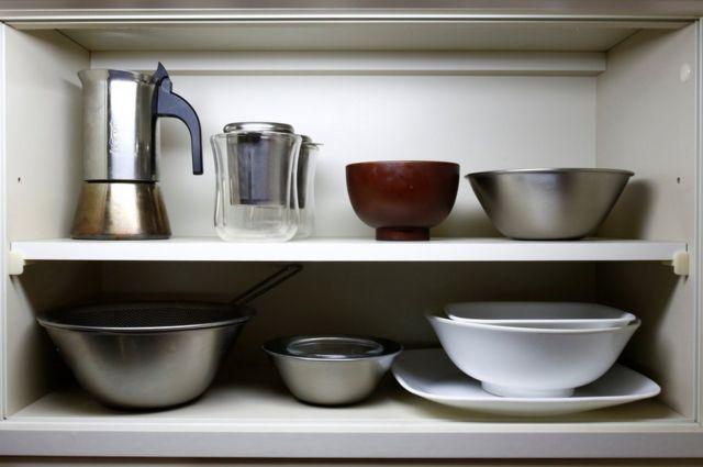 Tazas y otros utensilios en el armario de la cocina del apartamento de Fumio Sasaki.