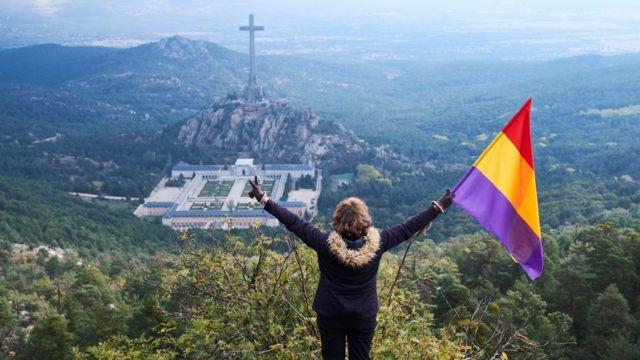 Mujer con la bandera republicana viendo el Valle de los Caídos