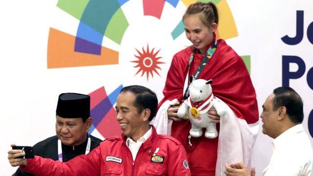 Tổng thống Indonesia Joko Widodo chụp hình với huy chương vàng pencak silat Wewey Wita