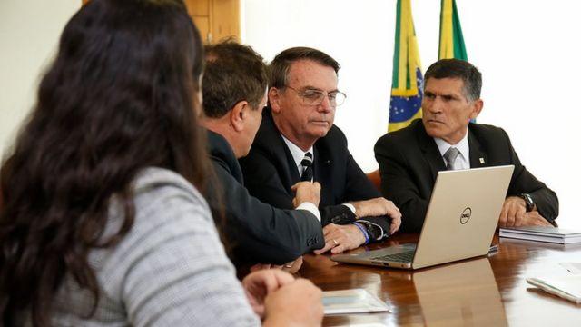 Bolsonaro e Santos Cruz sentados à mesa diante de laptop em reunião