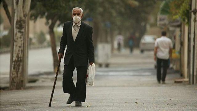 مرد مسنی با ماسک در هوای آلوده شهر اراک
