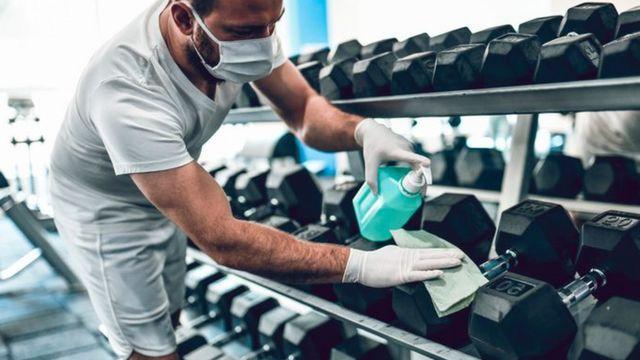 Homem de máscara segura pote com álcool e desinfeta uma série de halteres numa academia