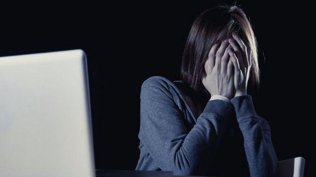 Mujer cubriéndose la cara frente a una computadora