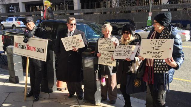 У здания окружного суда собрались несколько человек с плакатами в поддержку Флинна