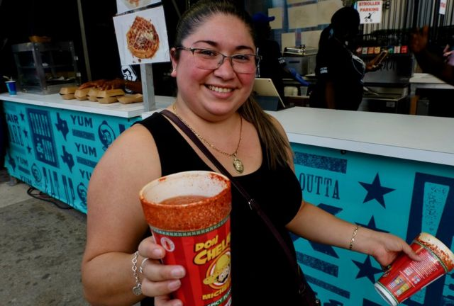A woman holds a large paper cup filled with a red liquid. The rim has been dipped in spices
