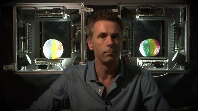 BBC Click's Spencer Kelly sits in front of two boxes containing a ball