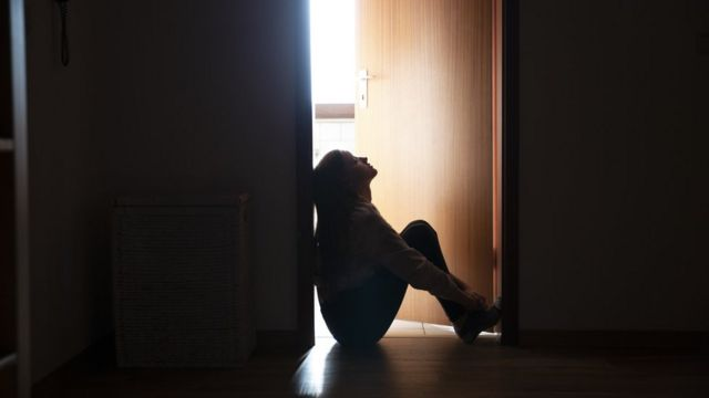 Mujer sentada en el umbral de una puerta a oscuras