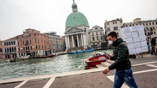 Homem andando com máscara em Veneza.