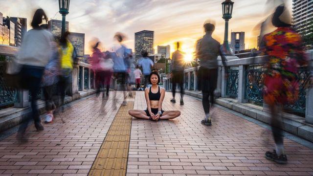 Mujer meditando en la calle.