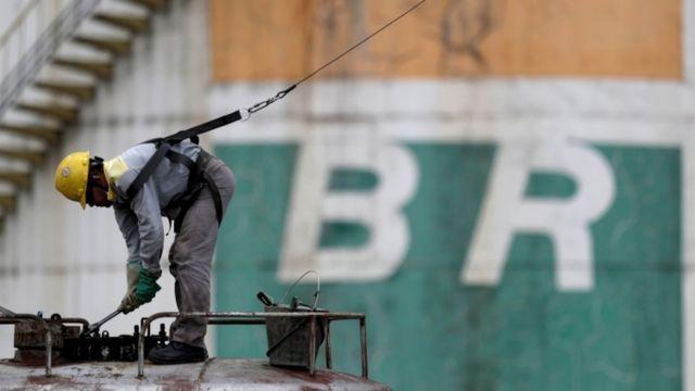 Operário agachado e trabalhando em frente a logo da Petrobras pintado no muro