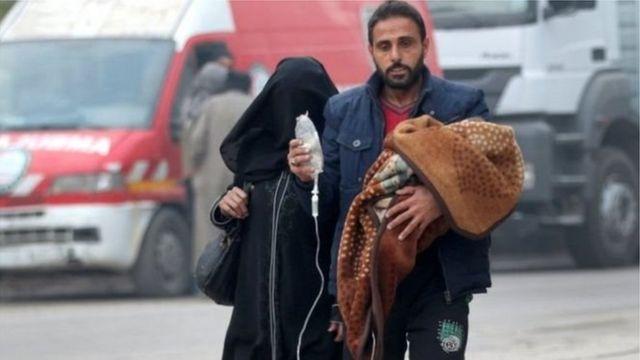 رجل يحمل طفله المريض