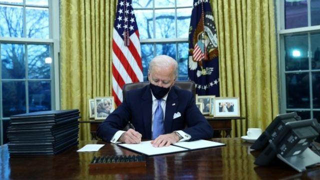 Biden desde la Oficina Oval firmando órdenes ejecutivas.