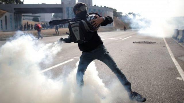 Manifestante da oposição lança gás lacrimogênio em Caracas