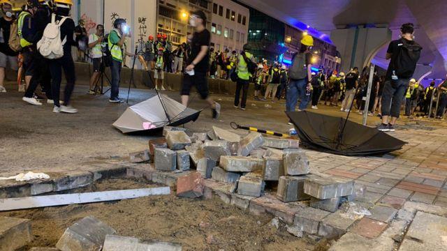 不少示威者从路边寻找砖头。