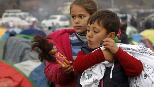Refugee children walk through a makeshift camp at the northern Greek border post of Idomeni, 16 March 2016.