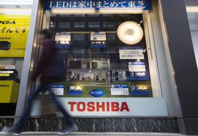 คนเดินผ่านหน้าร้านขายผลิตภัณฑ์โตชิบา