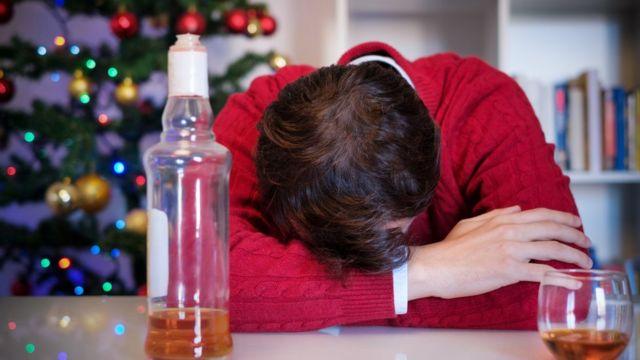 Homem dormindo em cima da mesa com garrafa de bebida alcoolica na frente e árvore de natal atrás