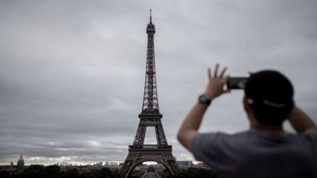 Homem fotografando a Torre Eiffel