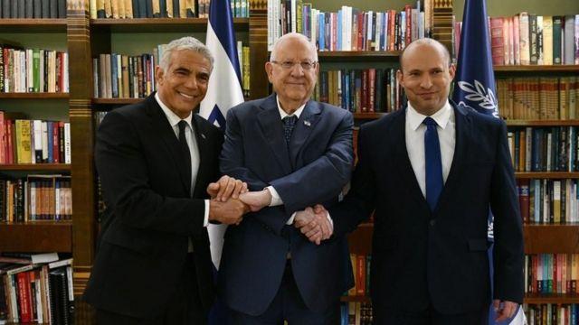 Israeli President Reuven Rivlin holding the hand of new Prime Minister Naftali Bennett (right) and Foreign Minister Yair Lapid.