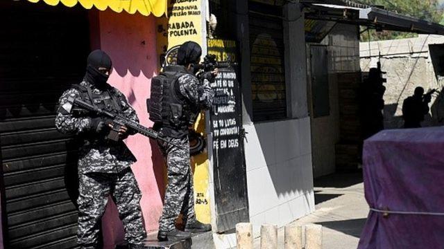 Policiais civis se protegem nos muros de estabelecimentos comerciais durante a operação