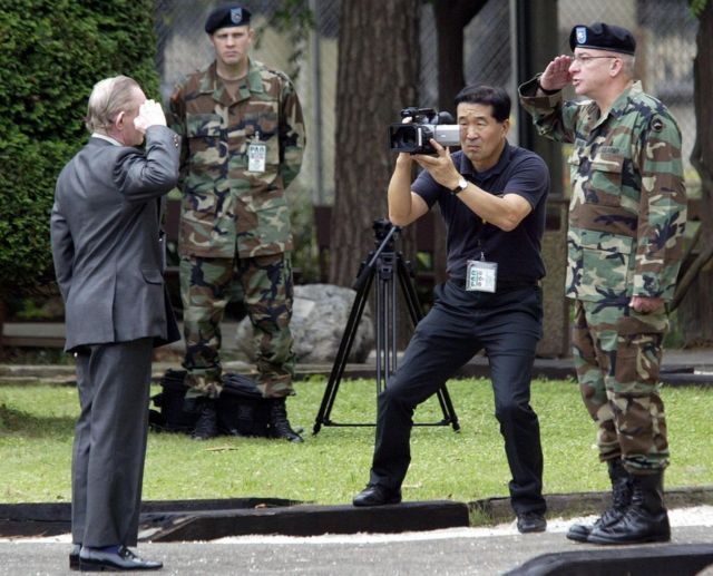 Charles Jenkins salutes Lieutenant Colonel Paul Nigara, as he is return to US military control at Camp Zama in Japan, on 11 September 2004.