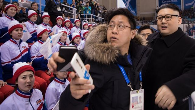 Some cheerleaders look at a Kim Jong-un impersonator disapprovingly whilst others look at the hockey match