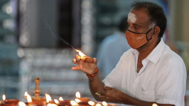 श्रीलङ्काको कोलम्बोस्थित हिन्दु मन्दिरमा दियो बाल्दै एक भक्तजन
