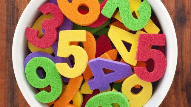 Números de brinquedo coloridos em uma tigela